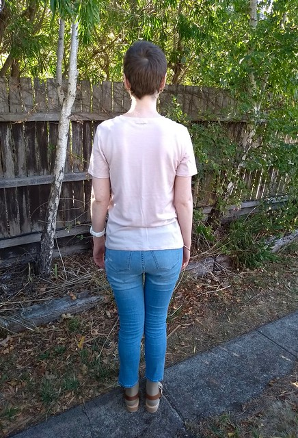Woman stands in front of garden fence. She wears pink merino knit tee, light blue jeans and clogs.