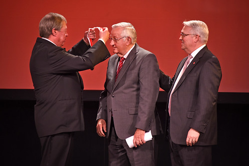 Board of Trustees chair Jimmy Clark (left) places the Watauga Medal over the head of 2018 recipient Bill Collins as Chancellor Randy Woodson (right) looks on.