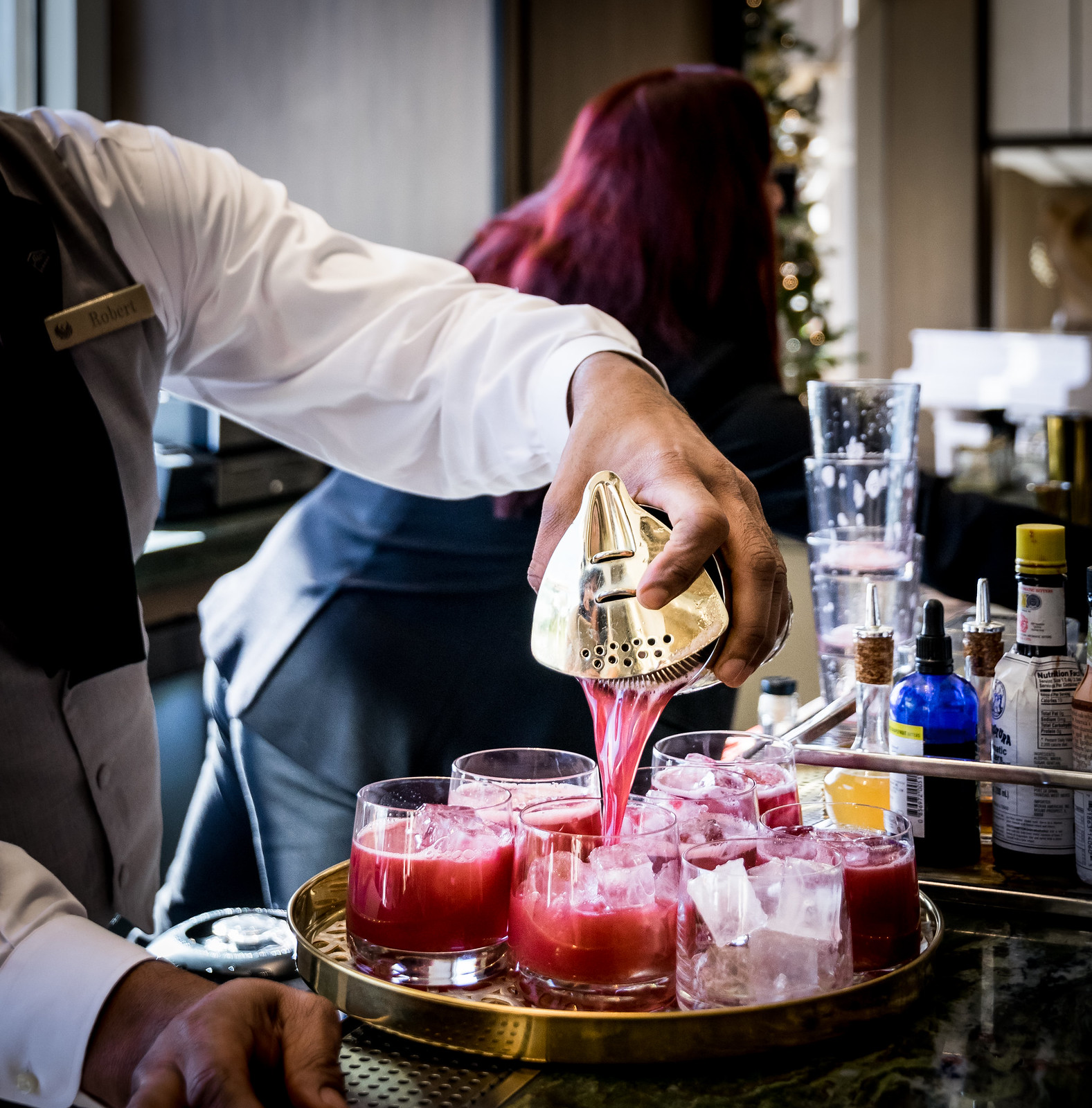 Robert pouring a round of Cortez cocktails: tequila & mezcal, hibiscus syrup, lemon,  and orange bitters