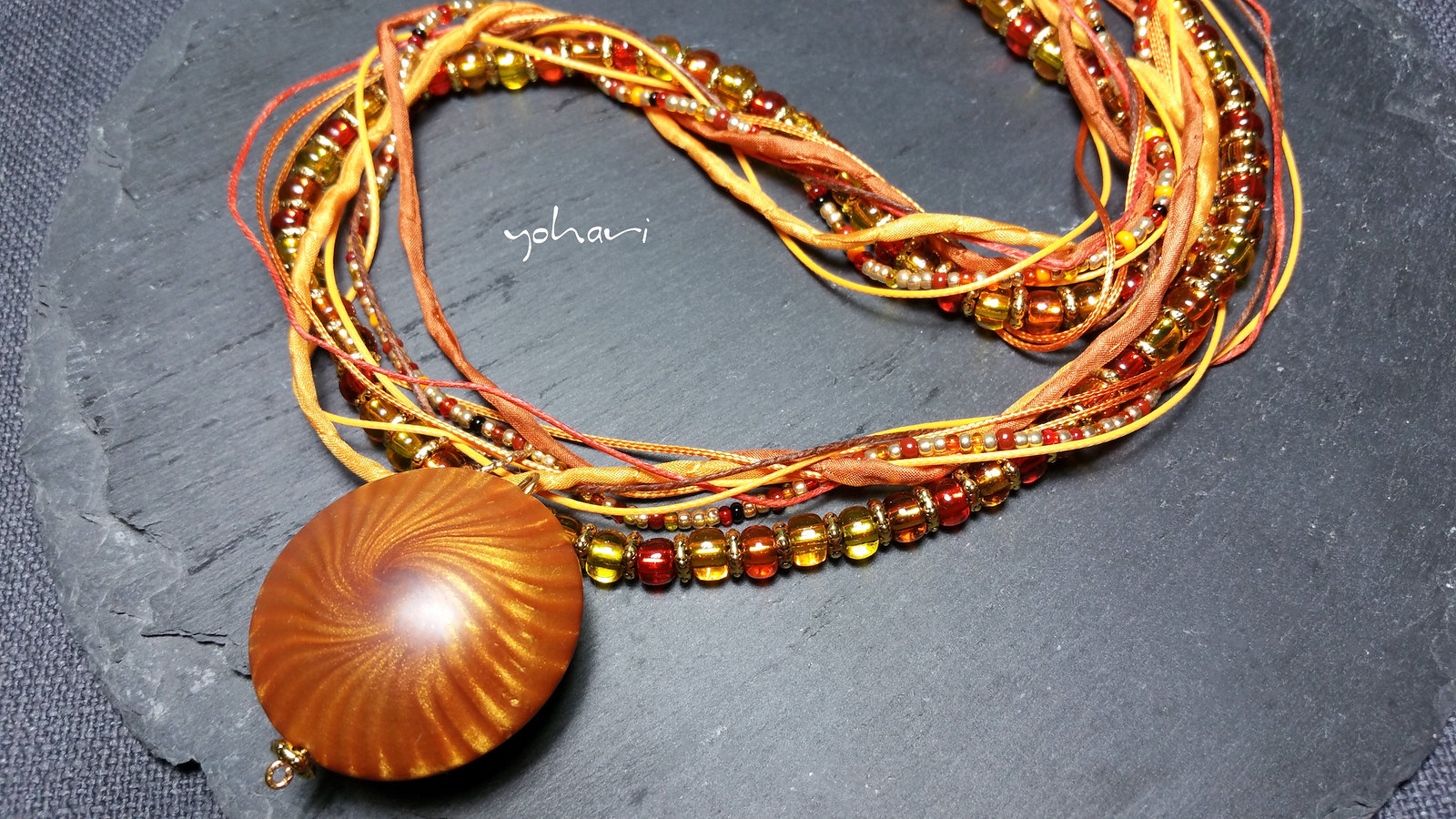 a golden necklace with polymer clay pendant