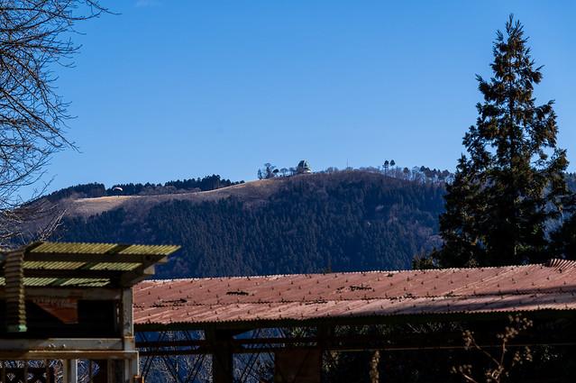 朽ちた茶屋跡の屋根越しに堂平山@定峰峠