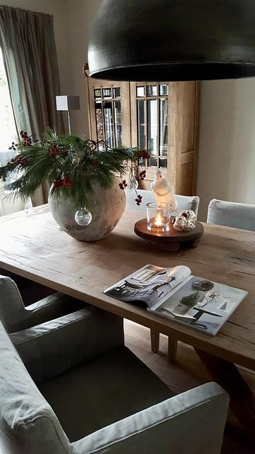 Kerststuk in kruik op eetkamertafel