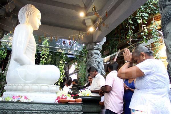 Buddhis Sri Lanka melakukan puja di hadapan rupaka Buddha di hari pertama Tahun Baru sekaligus perayaan Duruthu Poya.