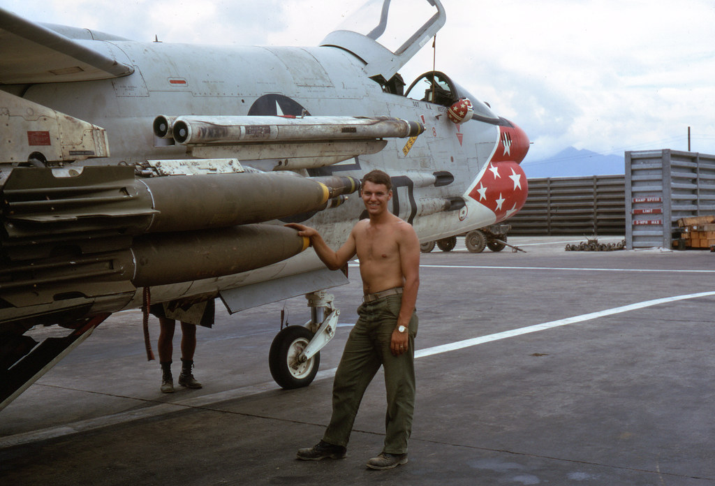 1967, August. US Marine F8-Crusader from Marine All-Weather Fighter Squadron 235 (VMF(AW)-235) (tail code DB) at Da Nang Air Base, SVN. Cpl. Jerry W Lemke standing by plane loaded with Mk-82 Snakeye bombs & Zuni rockets. Photo Courtesy of Deegan, Victor A