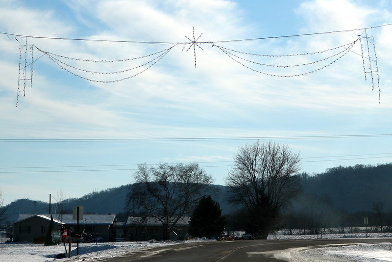 white strands across the road that look like bunting, with one white wire star in the center