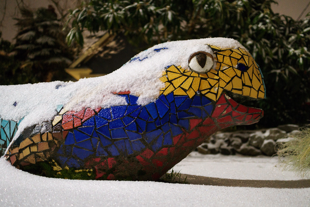 A dragon statue is lightly dusted in snow in the Irvington neighborhood of Portland, Oregon