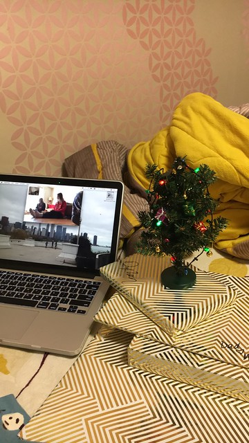 A laptop open with FaceTime pulled up. A miniature Christmas Tree sits next to it on top of gifts.
