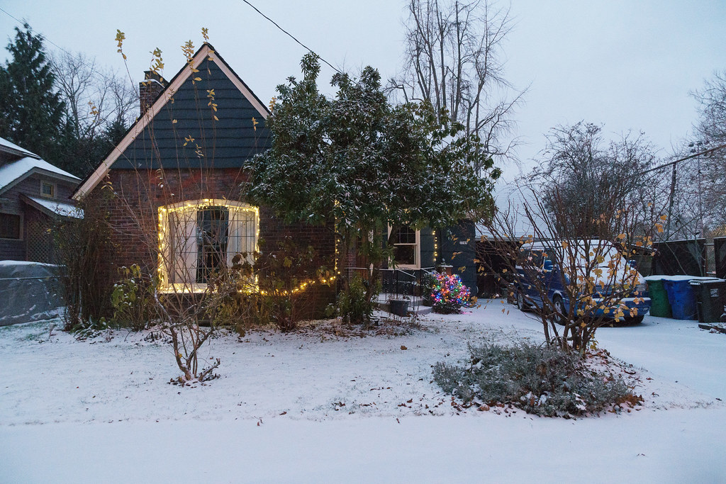 A home in the Irvington neighborhood is covered in Christmas lights and snow in Portland, Oregon