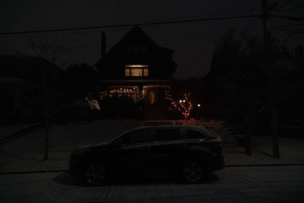 A house is lit up with Christmas lights in an otherwise dark neighborhood