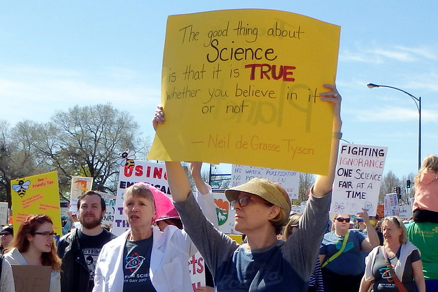 closeup of a marcher holding a yellow sign - The good thing about science is that it's true whether you believe in it or not