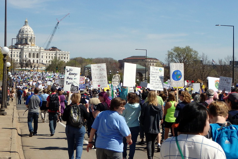 large group of people, many holding handmade signs, walking toward the capitol building