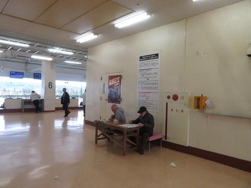金沢競馬場の3階にある机で予想する人々