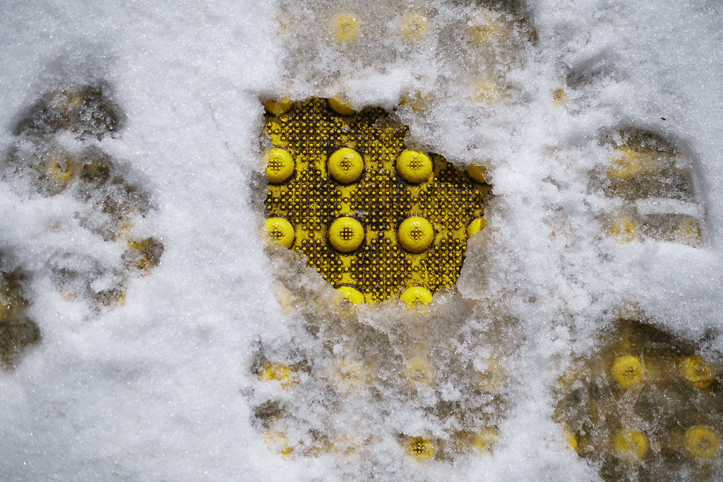 Yellow bumps on the ramp from the sidewalk to the street emerge from the snow in the Irvington neighborhood of Portland, Oregon