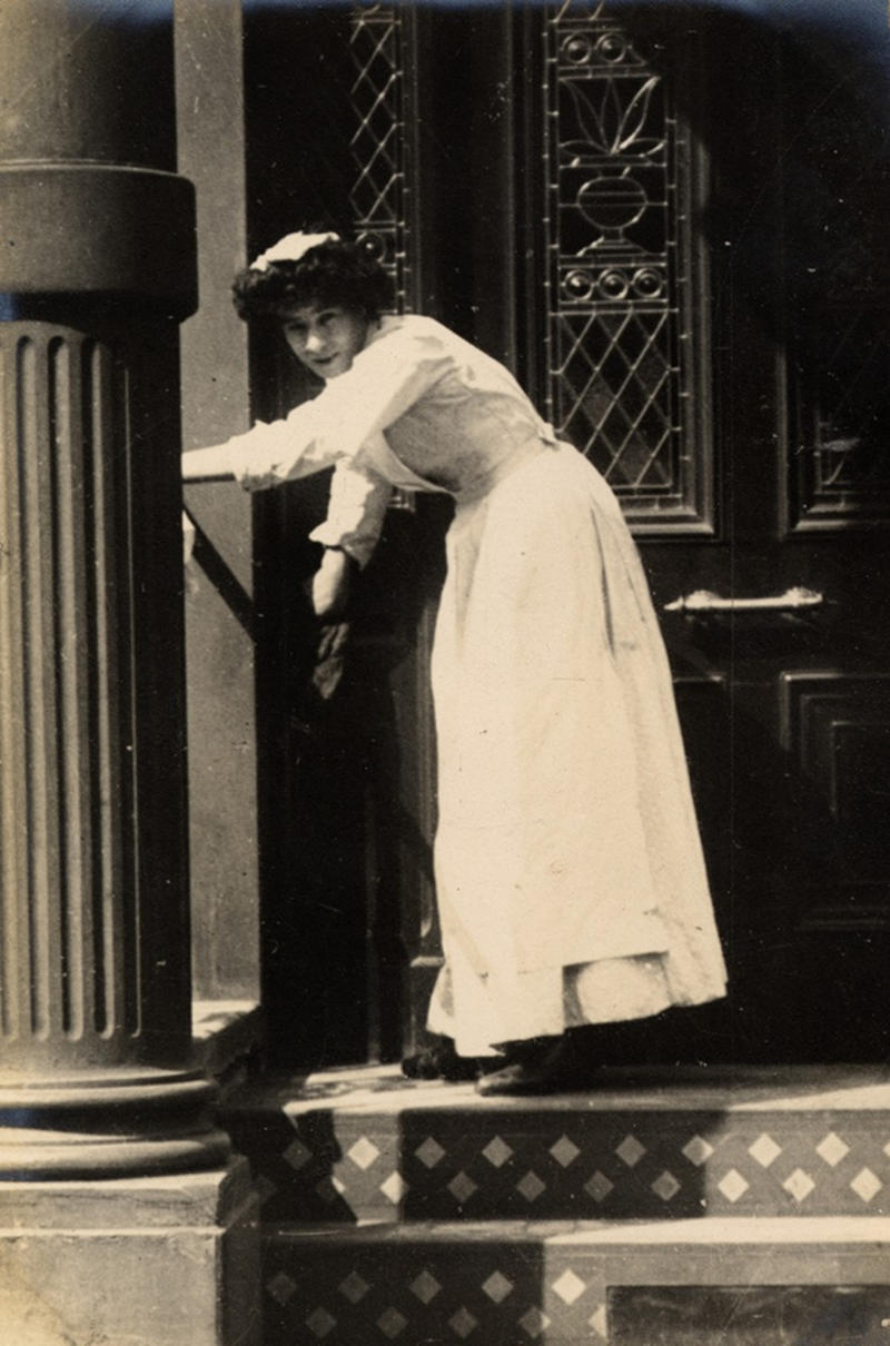 One step at a time. The tedious job of cleaning the porch steps, 1906
