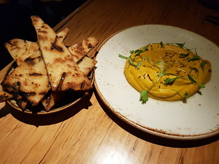Roast carrot, white bean and saffron dip with cumin seeds and flat bread at Transformer