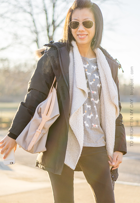 black parka, sherpa lined open cardigan sweater, gray graphic tee with party animals, black jeans, gray and beige tote