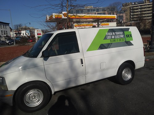 "A Russia Today news vehicle with an ""ad"" making fun of US concerns about Russian involvement in US politics"