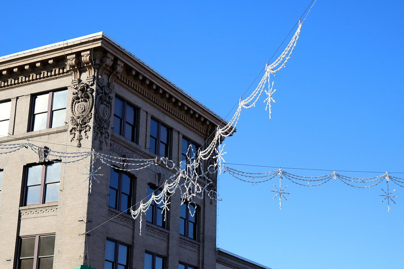 looking up at a white light decoration that comes from four corners and meets in the middle, with multiple strands that look like bunting and two stars dangling on each side
