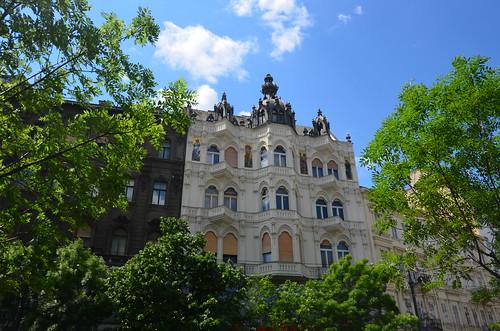 Blick durch Bäume auf ein nobles Wohnhaus in Budapest
