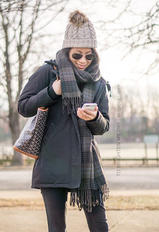beanie with pom, black parka, green plaid wool scarf, black jeans, patterned tote