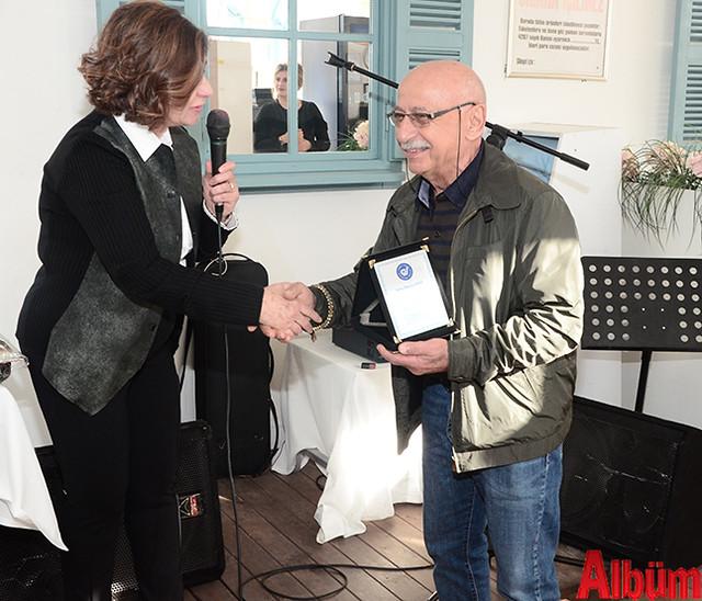 Nilgün Özcan, ÇYDD'ye desteklerinden dolayı 'Tüfekteki Gravür' kitabının yazarı Hüseyin Baba'ya plaket takdim etti.