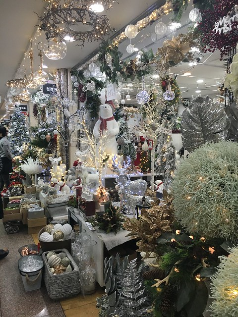A store front overflowing with silver and gold Christmas lights, ornaments and decor.