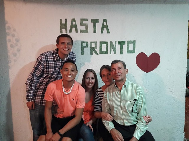 "Student and host family posing in front of a sign that reads ""hasta pronto."""