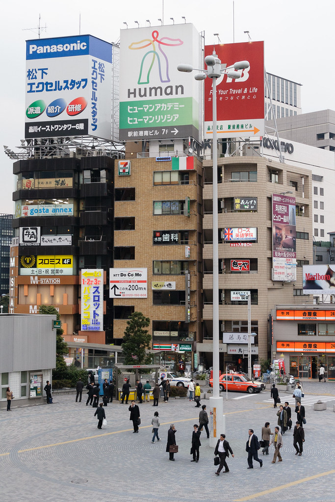 Residents of Tokyo walk past a building with a large sign saying 'Human'