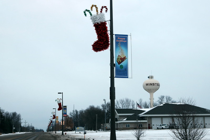 a red stocking with candy canes in the middle, a diagonal row of the same stockings to the bottom left, and the Winsted water tower at the right