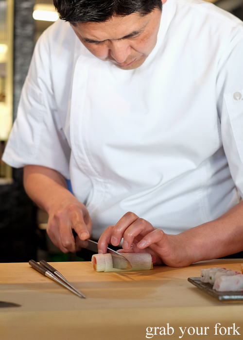 Chef Ryuichi Yoshii slicing a daikon sashimi roll at Fujisaki by Lotus at Barangaroo in Sydney