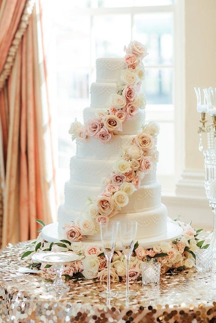 An elegant white wedding cake with cascading flowers, 7 tiers of grace and wonder! By Jennifer Kihneman of Pixie in the Oven