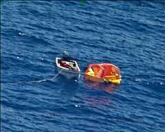 """CHUUK ATOLL, Federated States of Micronesia (Feb. 20, 2018) Three fishermen wait to be rescued after being  located by a P8-A Poseidon belonging to the """"Fighting Tigers"""" of Patrol Squadron (VP) 8. The mariners 19-foot skiff was first reported missing Feb. 12 after it failed to return from a fishing expedition near Chuuk Lagoon in the Federated States of Micronesia. (U.S. Navy photo/Released)"""