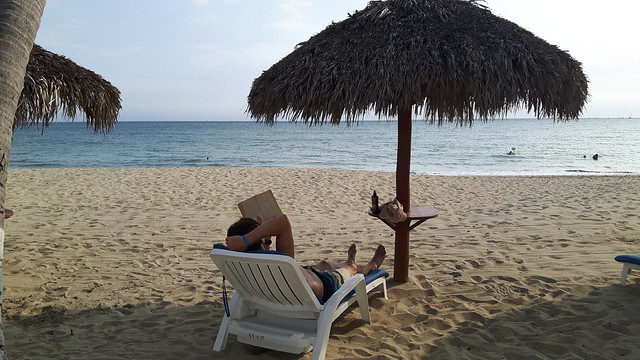 Terry sitting on the beach under a palapa reading a book.