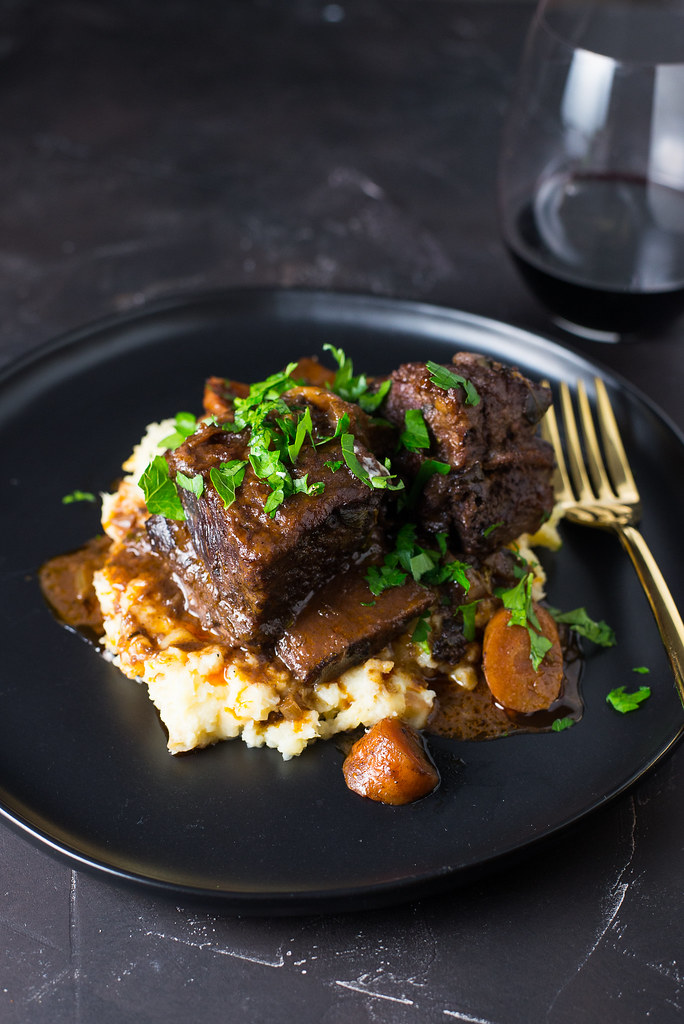 Classic Wine Braised Beef Short Ribs become incredibly tender and full of flavors from red wine, beef broth and fresh herbs. Serve with mashed parsnips for a truly delectable dinner.