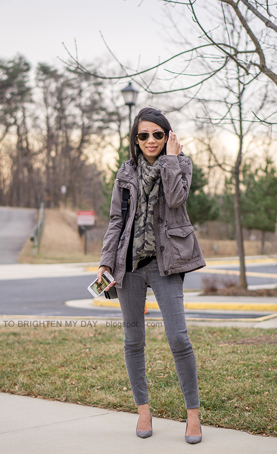 gray military jacket, camo printed scarf, black twist front top, gray skinny jeans, black shoulder bag, gray suede pumps