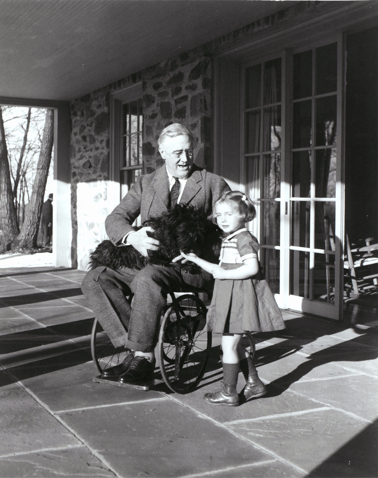 Rare photograph of Franklin D. Roosevelt, with Fala and Ruthie Bie, the daughter of caretakers at Hill Top Cottage in Hyde Park. The better of two extant photos of FDR in a wheel chair. Photo taken by his cousin Margaret Suckley (February 1941)