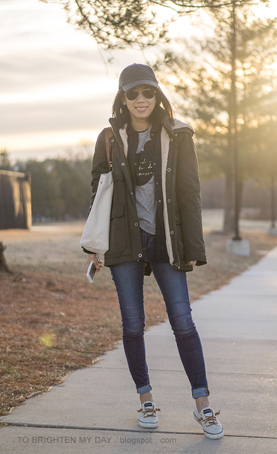 gray baseball cap, olive parka, black watch plaid shirt, Mickey Mouse graphic tee, skinny jeans, canvas tote, canvas sneakers
