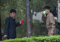 Two North Korean men drinking water in Mangyongdae which was the birthplace of North Korean leader Kim Il-sung, Pyongan Province, Pyongyang, North Korea