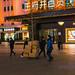 Chine,  Livreurs dans une rue commerçante de Pékin la nuit.