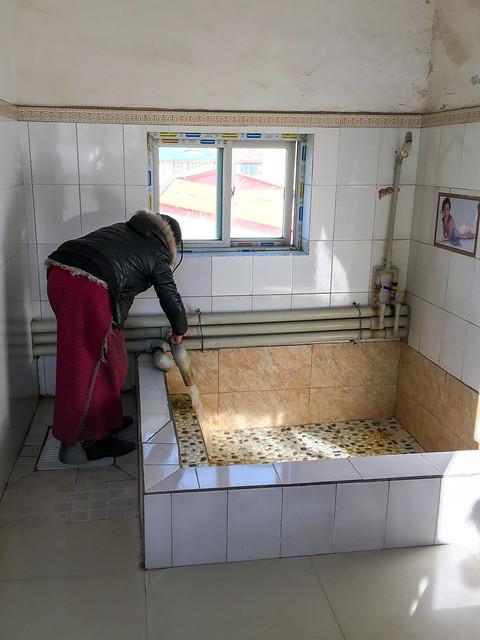 Preparing hot spring buth, Garzê 甘孜 個室温泉のバスタブにお湯を準備する女性