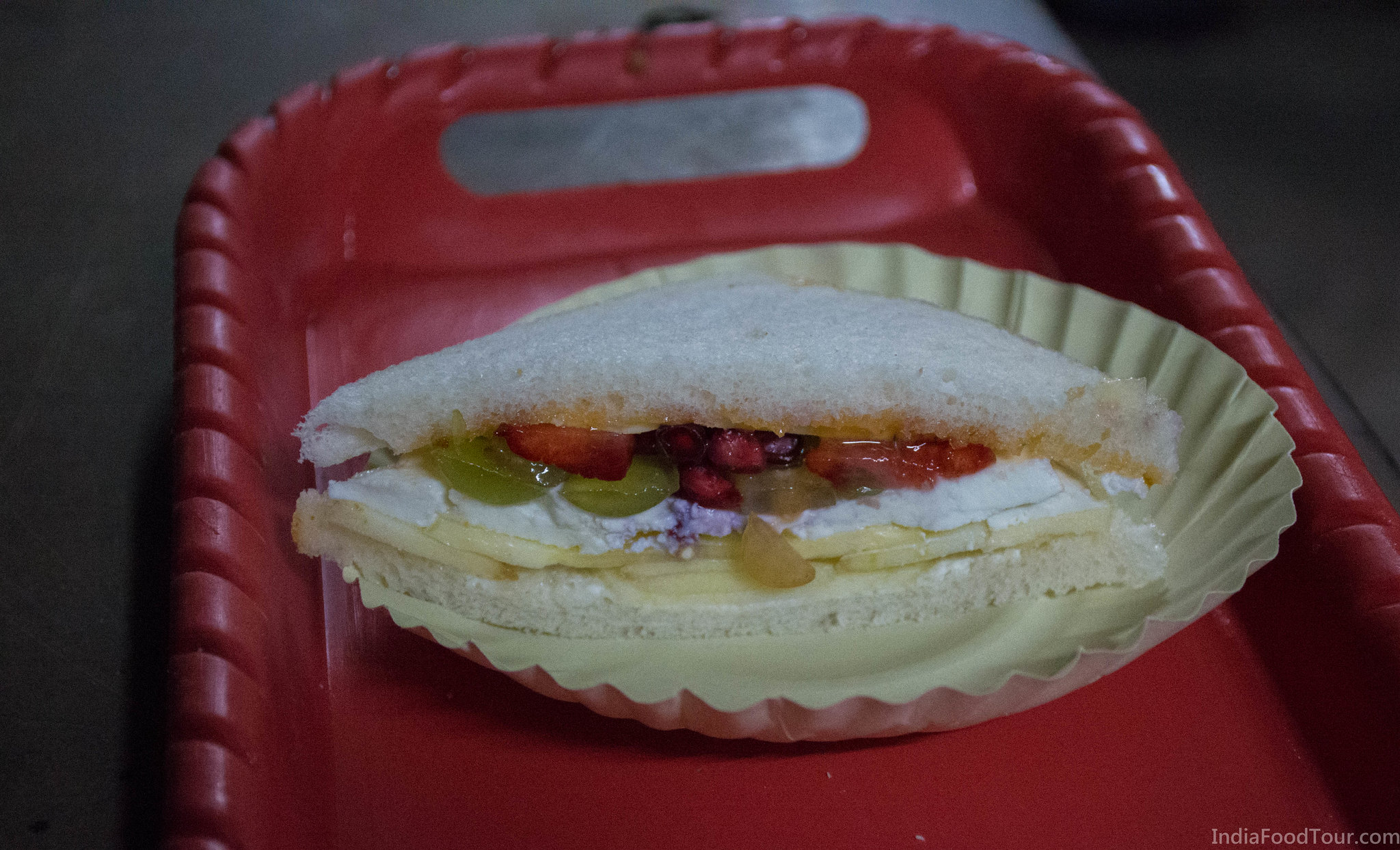 A very unique fruit sandwich sandwich with apple, pomegranate, pineapple, paneer, grapes and more