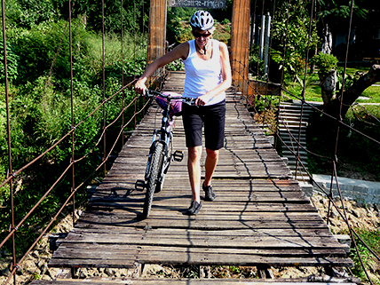 A Cyclist crossing over a suspension bridge in the outback of Thailand while on a cycling adventure in South East Asia.