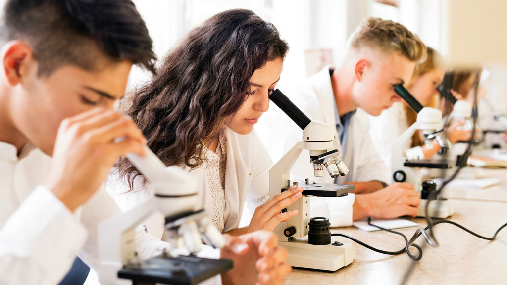 Students in a lab looking through microscopes