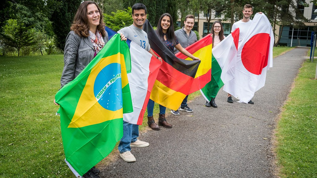 Six students each hold flag of Portugal, France, German, Spain, Italy and Japan.