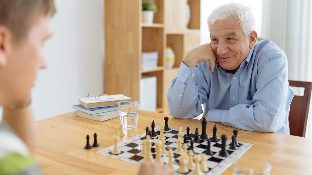A senior man playing chess with a young man