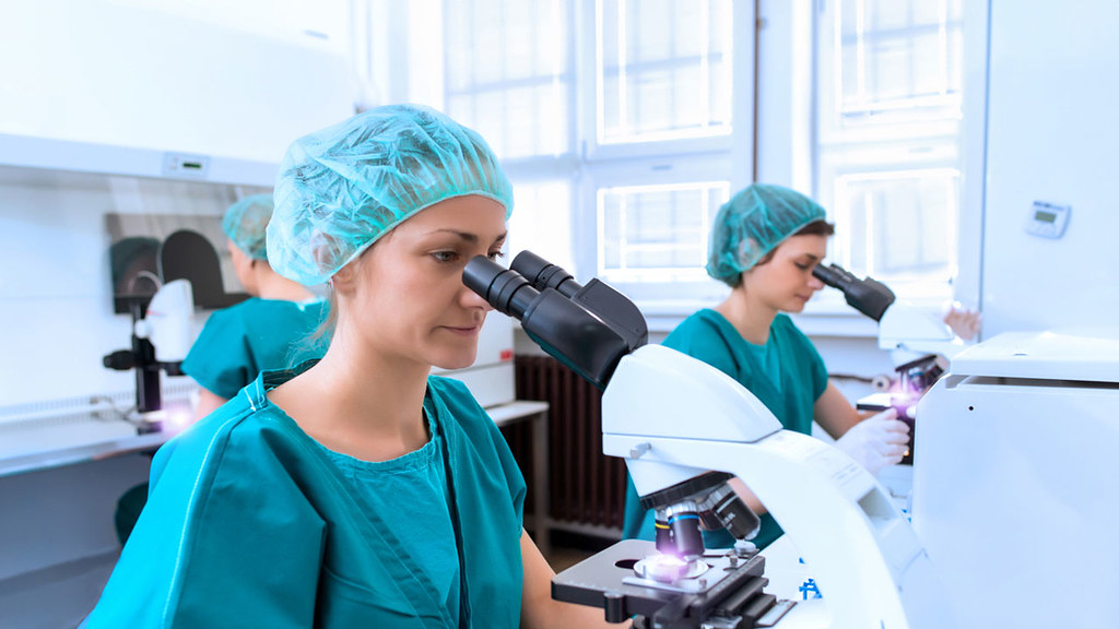 clinical staff look down a microscope