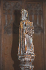 stall finial: celebrant holding a shield
