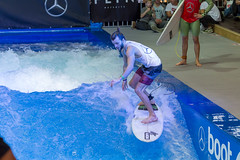 Young man riding the permanent wave of the surf machine Citywave at fair Boot Düsseldorf 2018