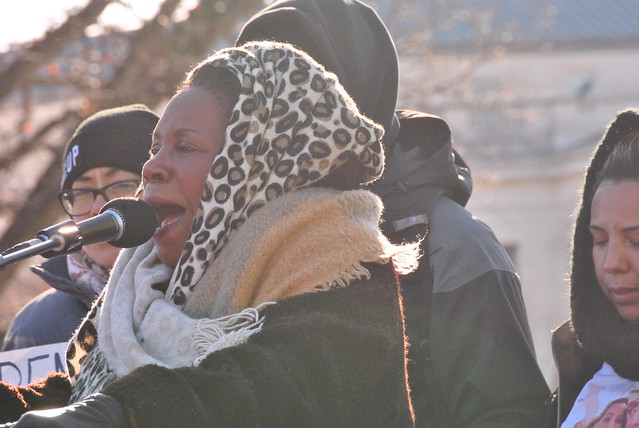 A woman at a microphone with a leopard-print head wrap and heavy coat.