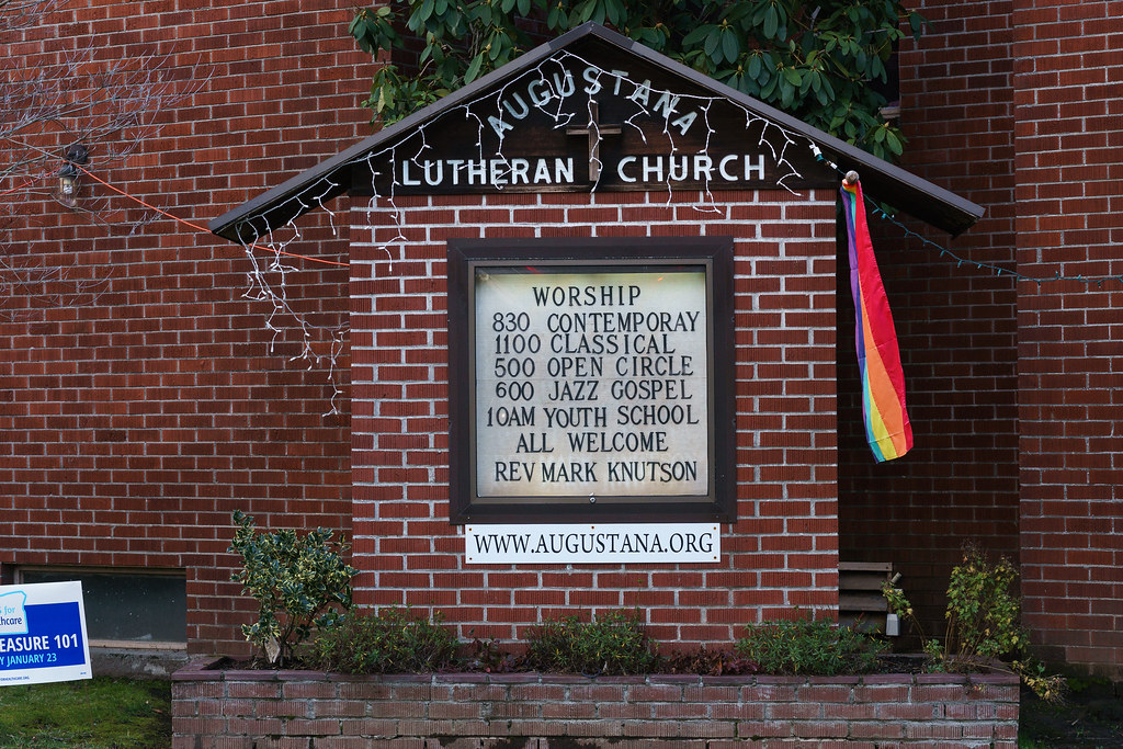 The rainbow flag flies at Augustana Lutheran Church beside the message 'All Welcome'